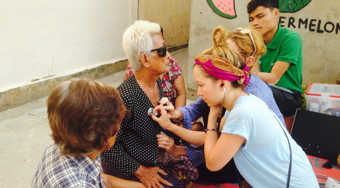 Interns learn how to check the vital signs of a patient as part of Public Health work for teenagers in Cambodia.
